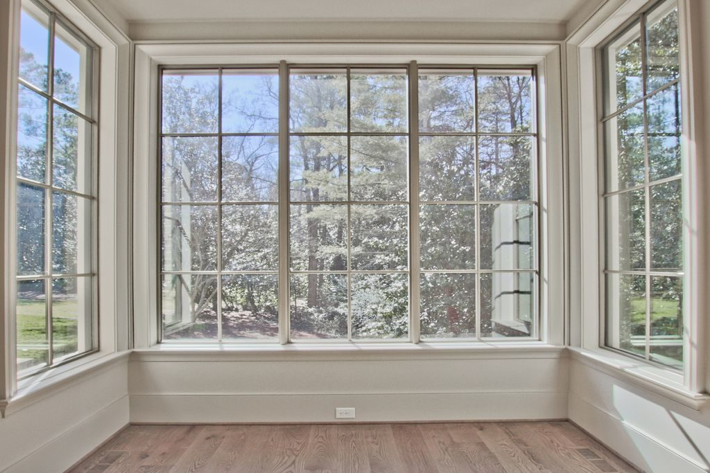 Bay window with hardwood floors and wooded view