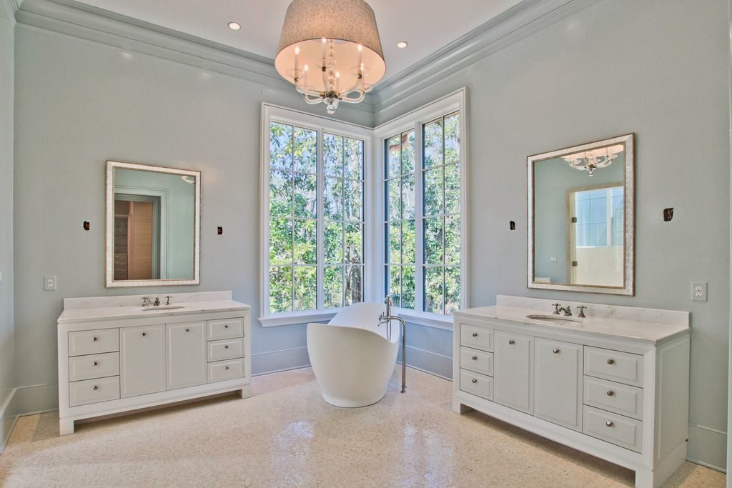 Open bathroom with deep tub and white cabinets